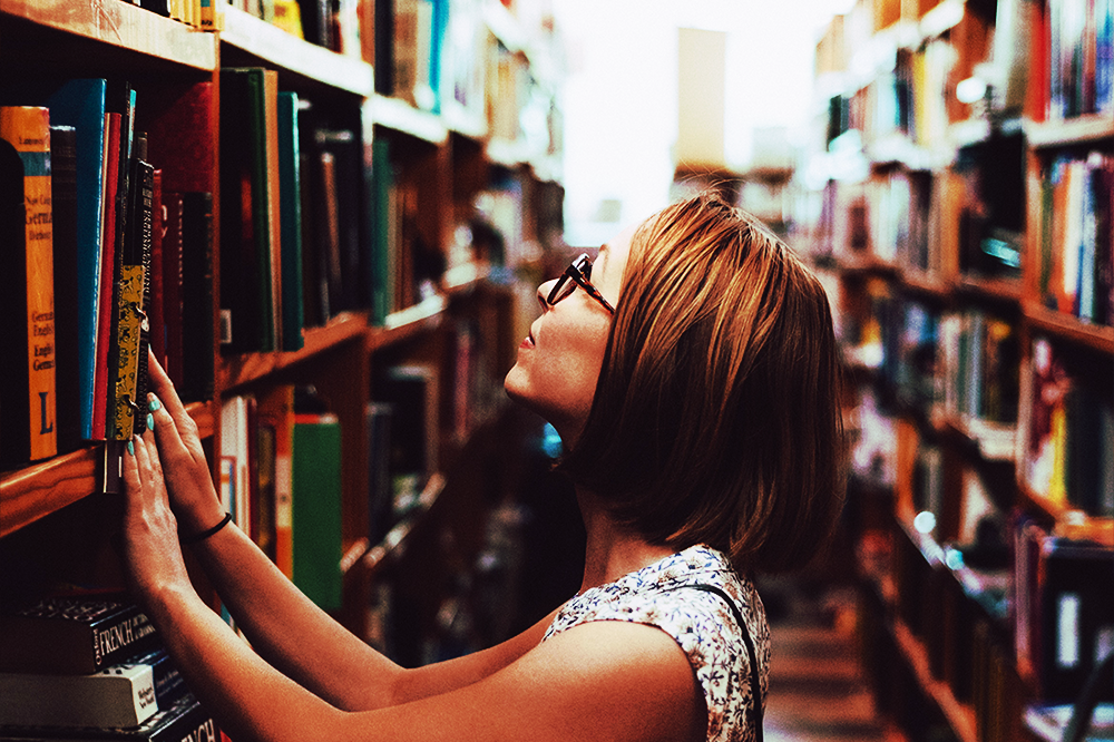 Woman looking at a stack of books in a library